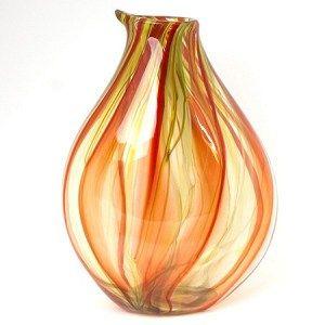 Vrijgeblazen vaas in glas. Als je naar deze vaas kijkt word je blij! In het transparante glas zijn de kleuren oranje/rood, groen en geel in wervelende lijnen te bewonderen. Haal de zomer en een warm gevoel in huis. Laat het zonlicht met dit kunstwerk spelen.