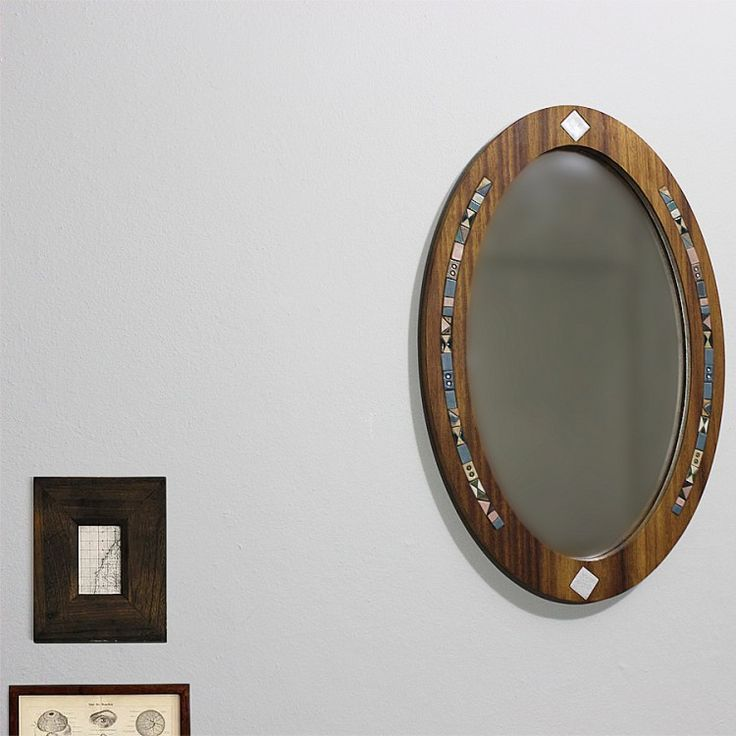 Handmade mirror made from iroko tree and surrounded by tiny ceramic tile. It is a specific product as a result of the elliptical structure.