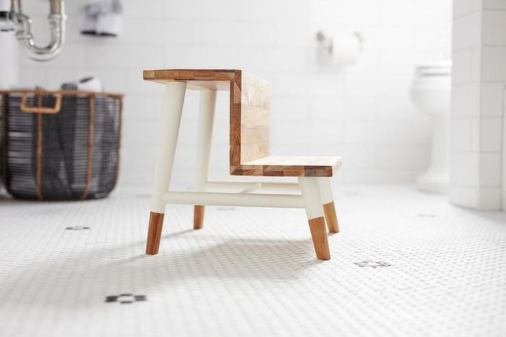 A Serena and Lily Teak Step Stool sits on white hexagon floor tiles in this well appointed boy's bathroom.
