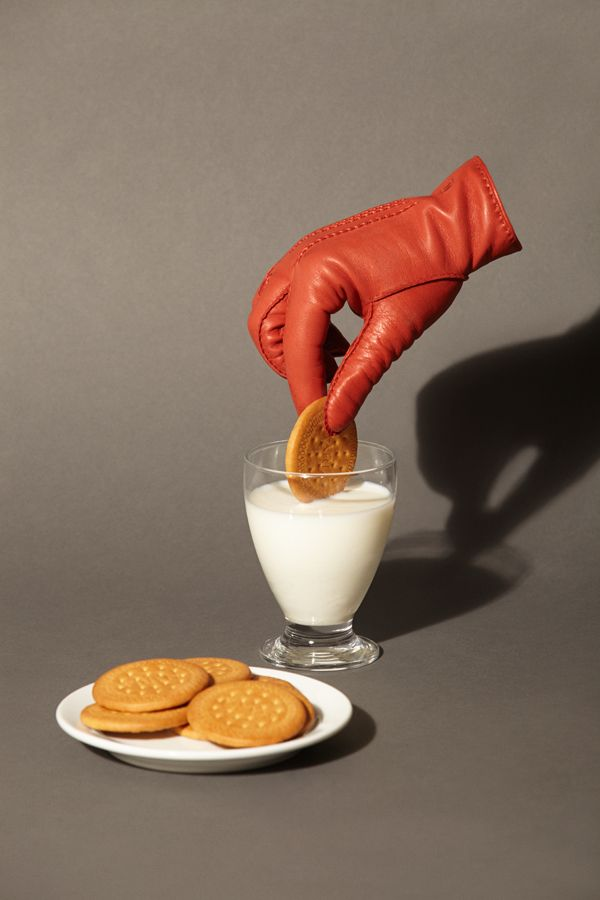 art direction | food still life photgraphy - hand with glove dunking cookie in milk