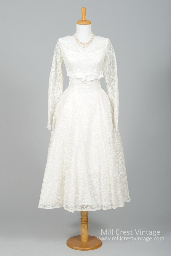 Designed in the 50's, this quintessential vintage wedding dress is done in a white floral embroidered lace over an acetate lining. The bodice offers a scalloped scooped neckline and v-cut scalloped ba