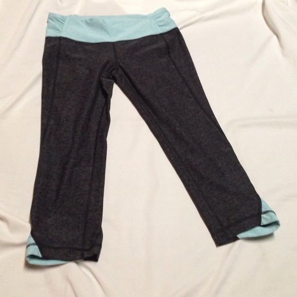 Under Armout studio luxe fitted capris Sz M All seasoned gear. 86% polyester 14% elastane.  Very new worn 2x. Color is dark grey and light blue. Bottom leg has some ruching (blue part) Under Armour Pants Capris