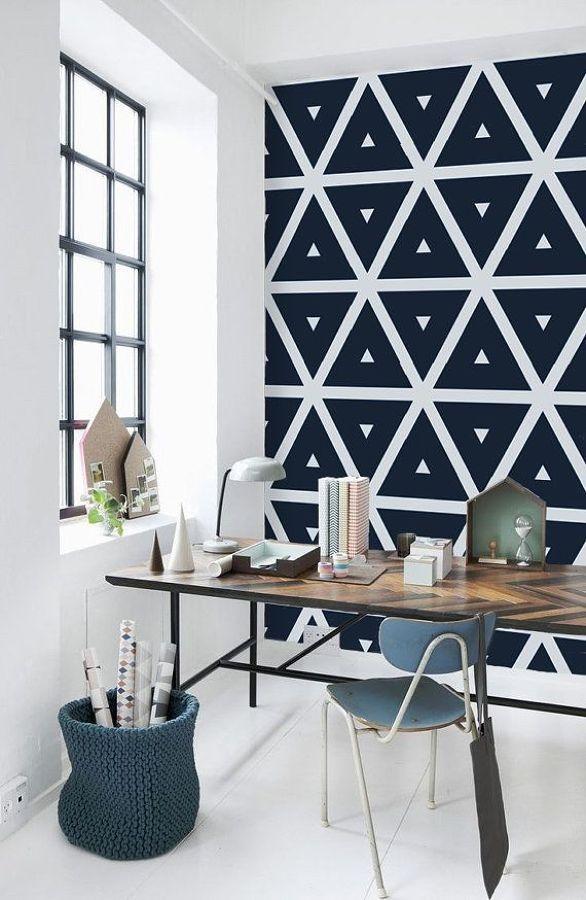 Un rincón con papel pintado oscuro y geométrico