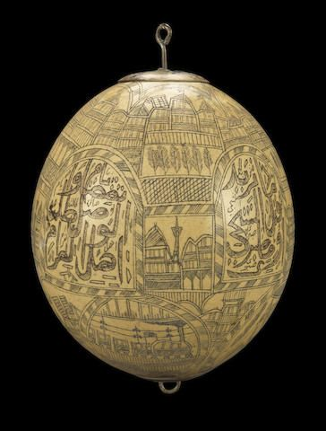 An Ottoman engraved ostrich egg hanging ornament by Hasan Fehmi Effendi - Turkey, dated Muharram 1278/July 1861 - profusely engraved and inlaid with black and red composition with a series of interlocking arched cartouches and roundels containing inscriptions, architectural scenes, a steam train, a soldier, a stork and a dervish, with gilt copper (tombak) mounts to each end 18 cm. high
