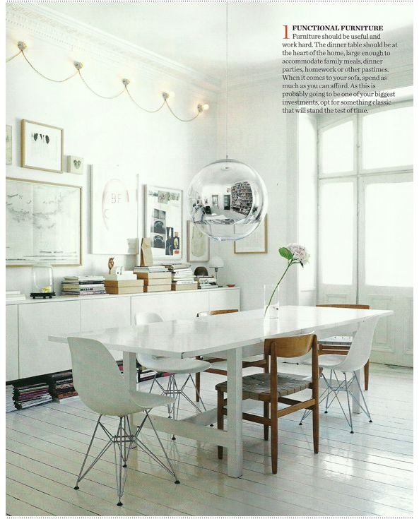 White dining room with mixed chairs. Elle Decoration  - Tom Dixon Mirror Ball  - Eames Chairs