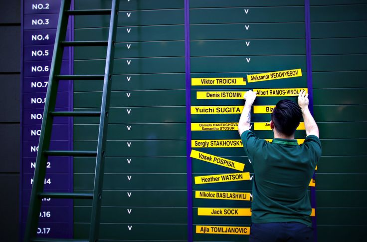 A member of ground staff updates a fixtures board on day two of Wimbledon tennis tournament on June 30, 2015 in London, England. The 129th tournament to be hosted at Wimbledon is due to run for two weeks from Monday 29th June
