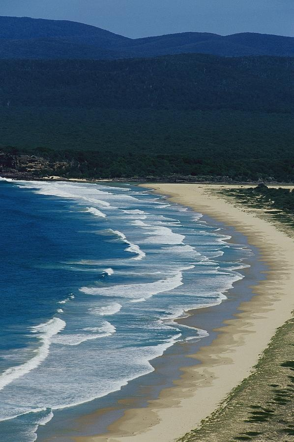 * Waves along a pristine beach in Disaster Bay at Ben Boyd National Park - New South Wales, Australia