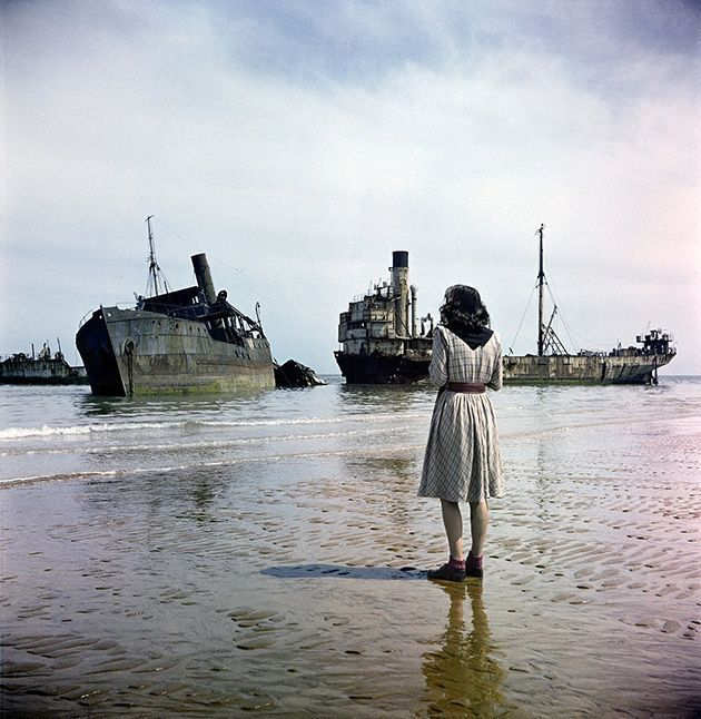 A woman looks out at ruined ships used in the D-Day storming of Normandy. Photograph by David Seymour, 1947.