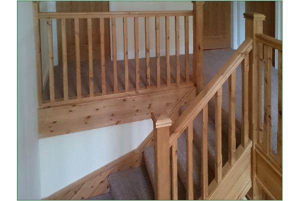 Trederwen View - this a double winder staircase with stop-chamfered newel posts and stop-chamfered spindles - all strings, newel posts, newel caps, handrail and baserail, spindles and aprons are in Redwood.