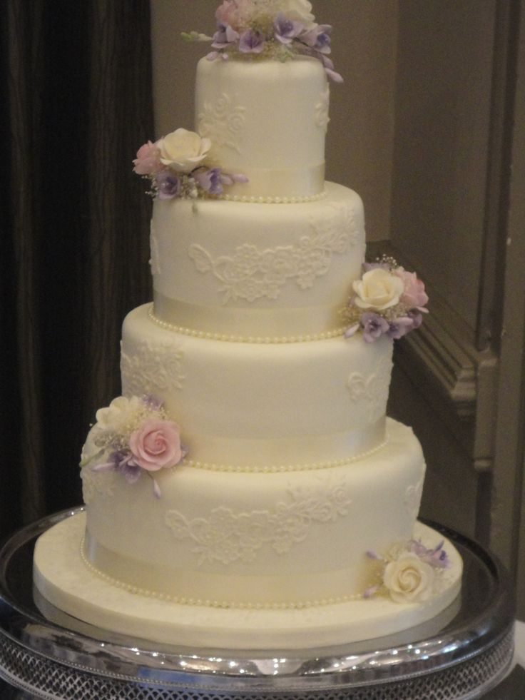 4 tier ivory iced wedding cake decorated with delicate edible lace on each tier, handmade sugar flowers in ivory and soft pink, and a small posy of sugar flowers on the top tier.