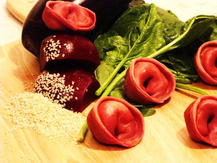 Empanadas de espinacas a la crema, cebolla morada confitada, semillas y aceite de sesamo