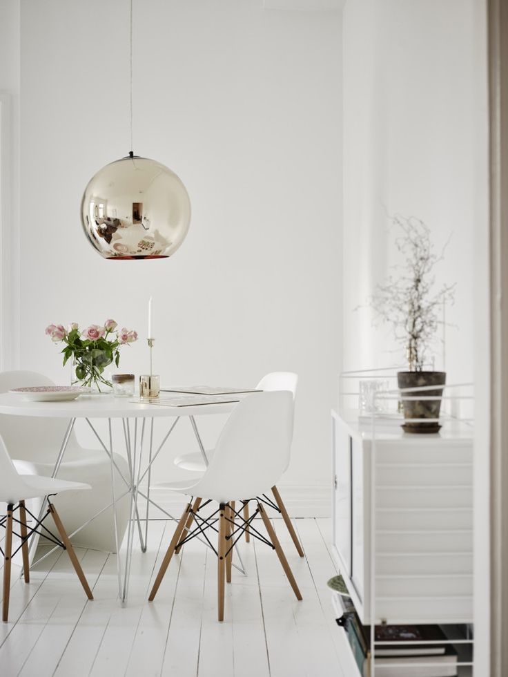 Clever use of space - Hege in France white dining room eames chairs panton, round dining table gold pendant light string shelves green plant:
