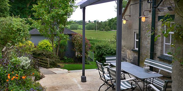The cottage veranda area, looking onto the stunning gardens and Summer House. Idyllic spot any time of the day.