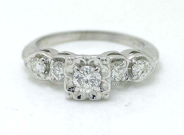 A beautiful engagement ring from the 1950s set in 14kt white gold that features a round brilliant diamond in the center that weighs approximately 0.35 ct. The center stone is accentuated by 4 smaller