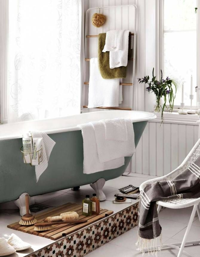 Badkar med tassar i ett ljust badrum med stort fönster.