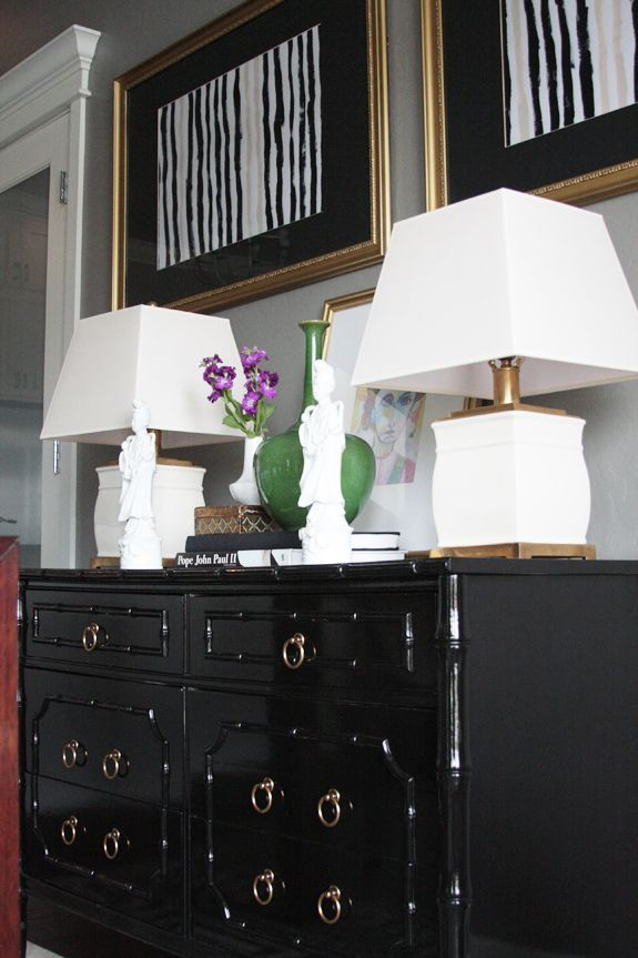 Black chest of drawers with white lamps, and gold accents