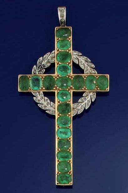 AN EDWARDIAN GOLD, EMERALD AND DIAMOND LATIN CROSS PENDANT. The cross set with oval-cut emeralds within a millegrain border, to a rose-cut diamond wreath and pendant loop, circa 1910.