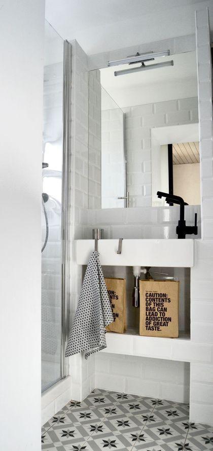 Une petite salle de bains blanche relevée de carreaux de ciment.
