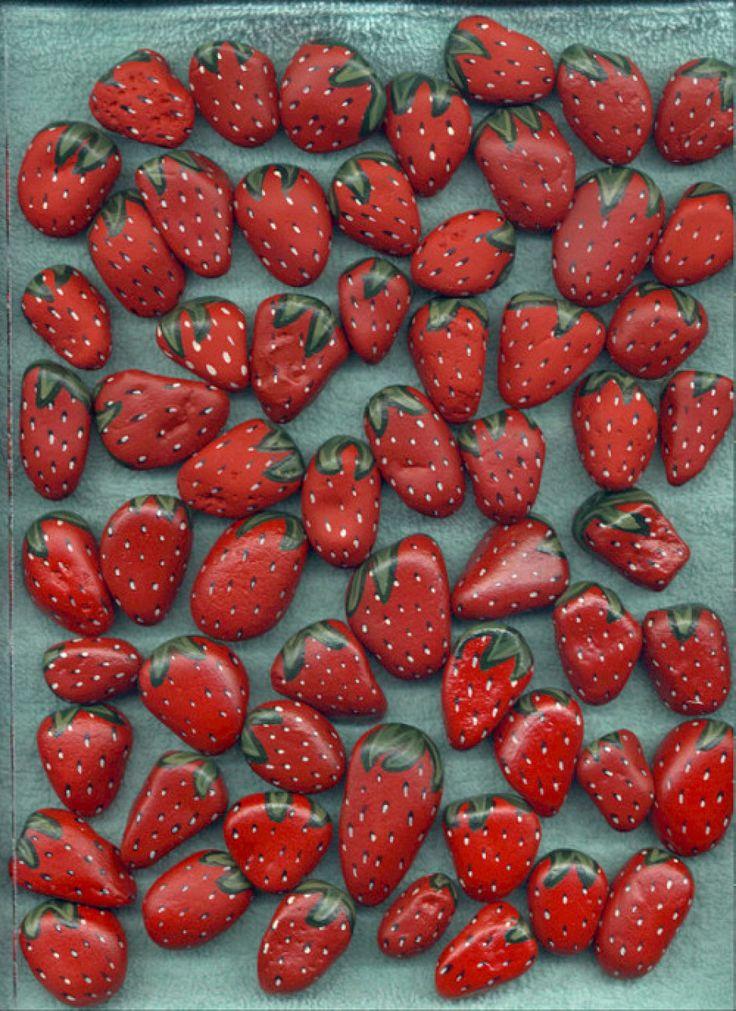Leg steentjes beschilderd als aarbeien rondom aardbeiplantjes om vogels te misleiden en weg te houden van de rijpe aardbeien
