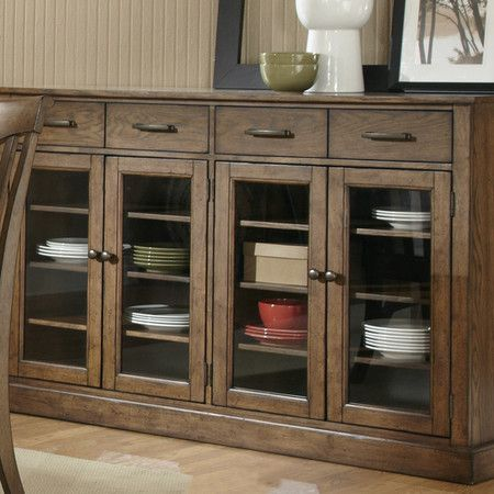 Showcasing a wood base and framed glass doors, this essential server is perfect for stowing spare dinnerware or table linens in your kitchen or dining room.