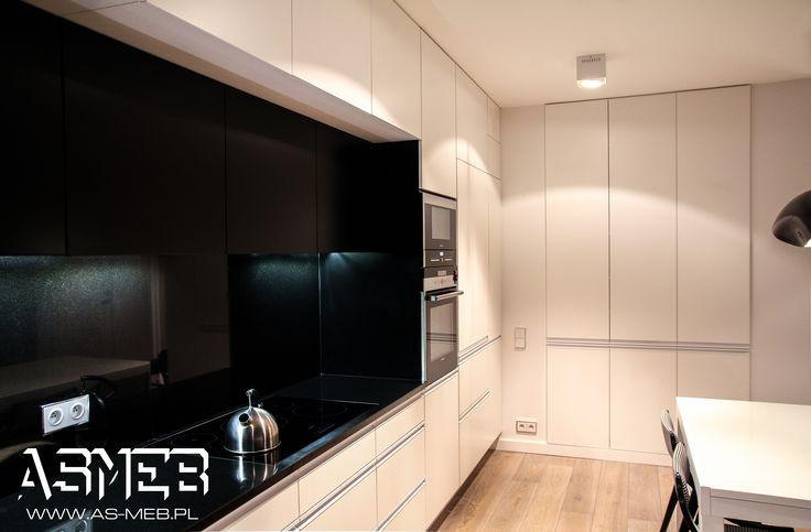 Zabudowa 525 cm szerokości. Dwie głębokości szafek górnych: płytkie lakierowane szafki w kolorze czarnym oraz głębokie lakierowane w kolorze białym. Blat wraz z okłądziną ściany - czarny granit.