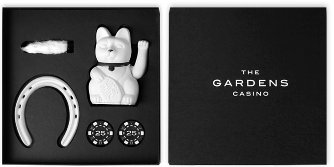 The Gardens Casino Invitation for Black Jackpot, a blackjack tournament at The Gardens Casino, includes a personal letter detailing the event, event poster, rabbit's foot, horseshoe, fortune cat, and 50 dollars worth of poker chips.