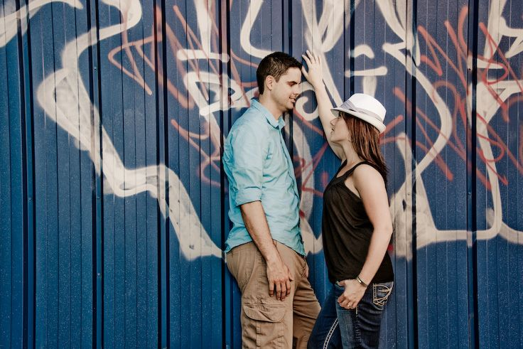 Regina, Saskatchewan Engagement Photography by Pure Photography & Design. Beautiful couple posing against a graffiti wall in an urban city. www.purephotographyanddesign.com  #reginaengagementphotography, #reginaengagementphotographer, #engagementphotographyideas, #reginaweddingphotographer, #reginaweddingphotography, #engagementphotography, #engagementpictures