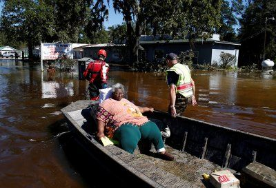 Disasters in 2016: Photos of devastation wrought by earthquakes, floods, fires and hurricanes:       Rescue personnel evacuate a resident by boat in the downtown area of Nichols, South Carolina on 10 October 2016   Randall Hill/ Reuters