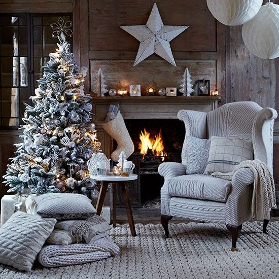 Country Christmas living room with wood panelled wall, fireplace, grey woven rug, cable-knit covered wing chair and Christmas tree