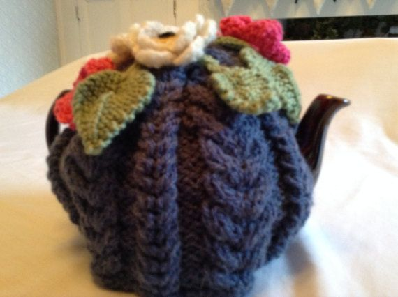 Teapot cosy which has been hand knitted in a cable design using chunky yarn. . Pink and cream crocheted flowers in double knit yarn decorate the cosy as do the knitted green leaves. The cosy fits a standard size teapot.