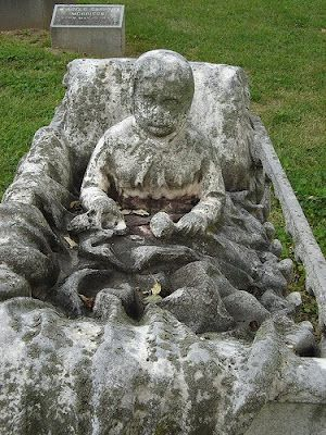 A sculpture of a child in a crib, covered with a blanket of stone. Calvary Cemetery, St. Louis, Missouri
