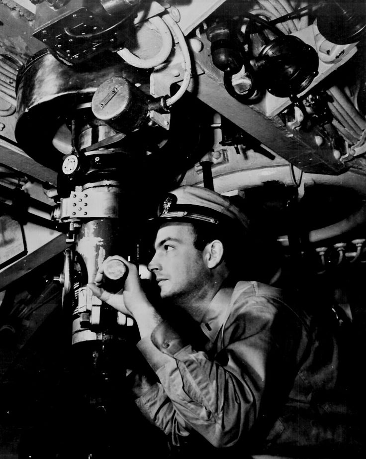 Officer at periscope in control room of submarine. 1942