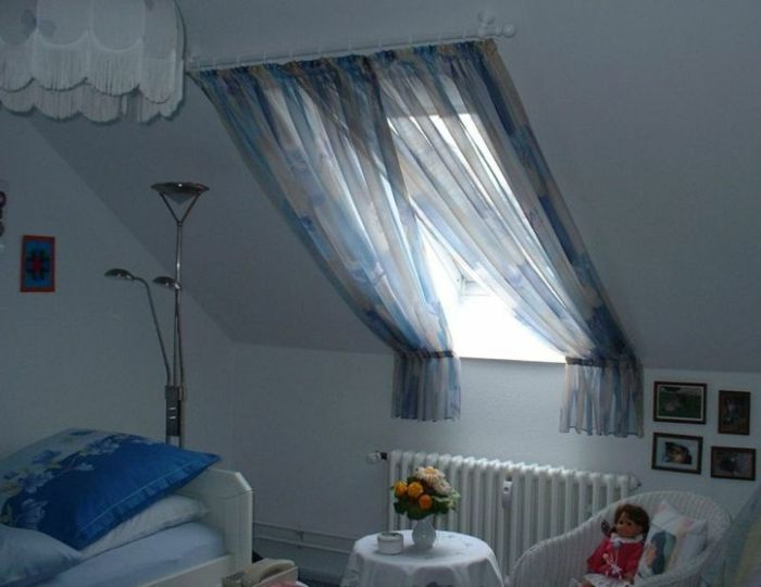 room with bed in pale and dark blue, small white round table and chair, sloping window with overlapping curtains, in pale blue and grey
