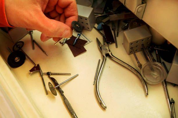 hand is holding dental tools dental prosthesis dentures prosthetics
