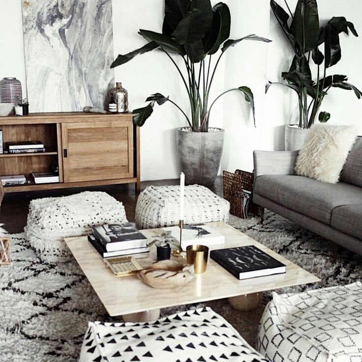 Contemporary eclectic design, white Interior, patterned rug, wood furnishings, abstract art, pouf seating, low seating area, Scandinavian style