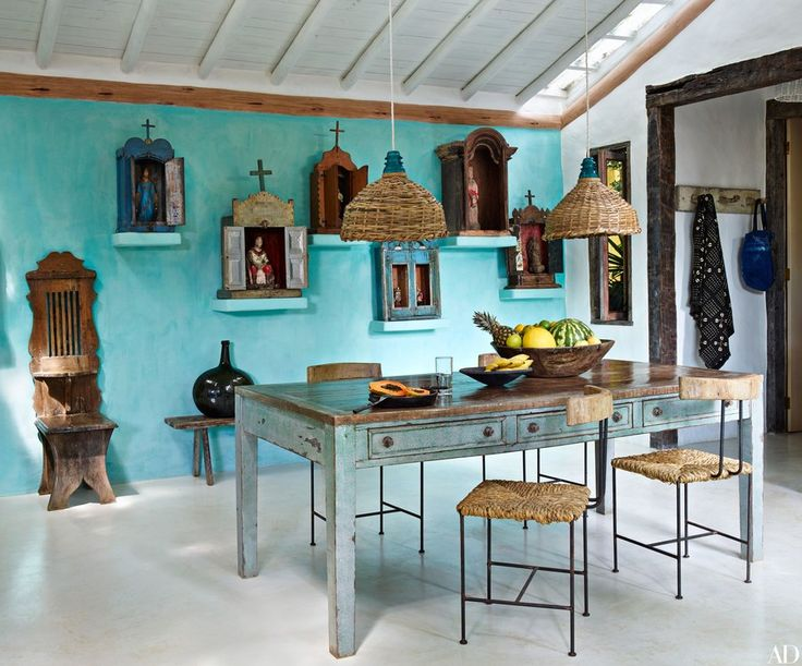 In the dining area of Anderson Cooper's Trancoso, Brazil, vacation home, an assortment of Brazilian devotional oratories and an antique confessional chair are arrayed against a turquoise wall; the ceiling lights and dining chairs are by Uxua Casa, the table is vintage, and the floor is waxed concrete.
