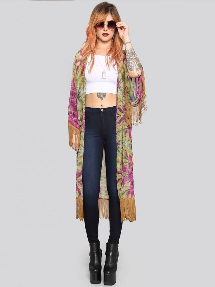 JAC VANEK Shades of green, purple, and gold come together in this tropical floral print kimono featuring three-quarter length sleeves, gold fringe on the hemline and cuffs, and an open front.  Pair it with a wide brimmed hat and leather pants for a nice fall transitional look.