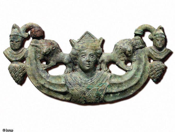 Applique en bronze montrant la déesse Cybèle, protectrice des enfants et des animaux, entourée de deux lions, avec son amant Attis coiffé d'un bonnet Phrygien. Famars.(Nord)..