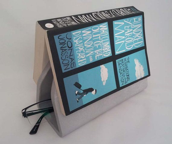 Concrete cast book wedge which holds your book page and glasses by Vincent Sawyer