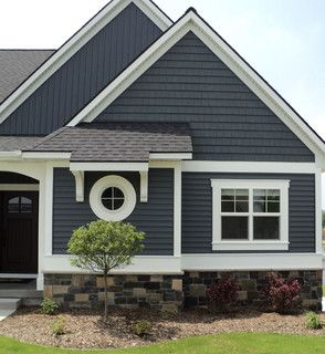 Dark blue/grey vinyl siding on a house with stone veneer around perimeter. White trim black roof The color is Harbour Blue, from Team Wholesale