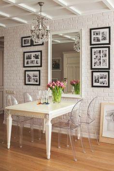 louis ghost chair, cadeira transparente na decoração, mesa branca encostada na parede, parede de tijolos a vista apintada de branco, quadros em preto e branco e espelho grande na decoração da sala de jantar, piso de madeira