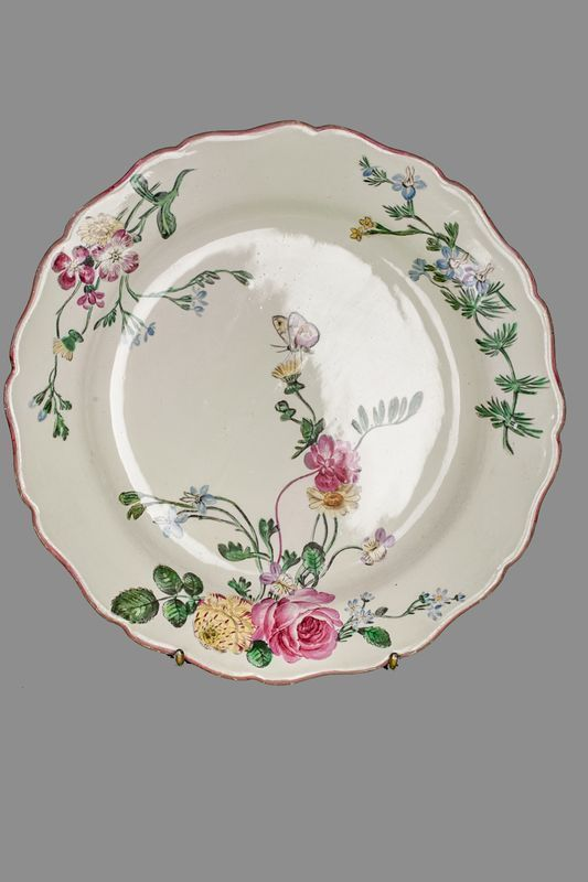 MARSEILLE  Assiette en faïence polychrome à décor floral et insectes. XVIII ème. Diam: 25 cm