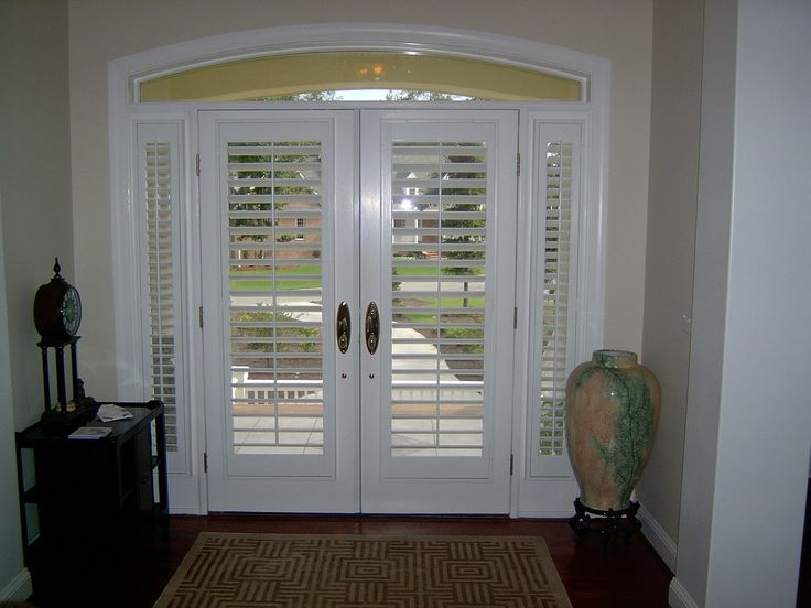 Interior view of plantation shutters on a glass front door for Wood doors and shutters