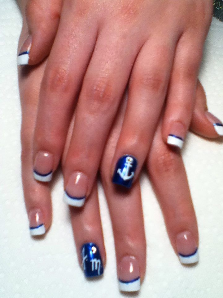 Acrylic nails with white tips, lined out in navy blue, Enhanced with full navy blue ring fingers with hand art of Anchor & crystal at the top and initials to honor a loved one.