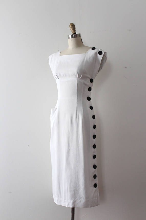 Seriously bombshell white wiggle dress from the 1950s. This dress features a flattering silhouette, an empire waist detail, and large black buttons down the side.