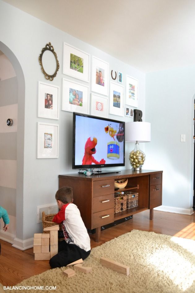 Never know what to do with that TV wall? Love this gallery wall laid out around the TV using children's art work.