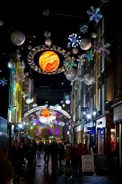 Pedestrians walk under the Christmas lights over Carnaby Street on November 23, 2010 in London, England.