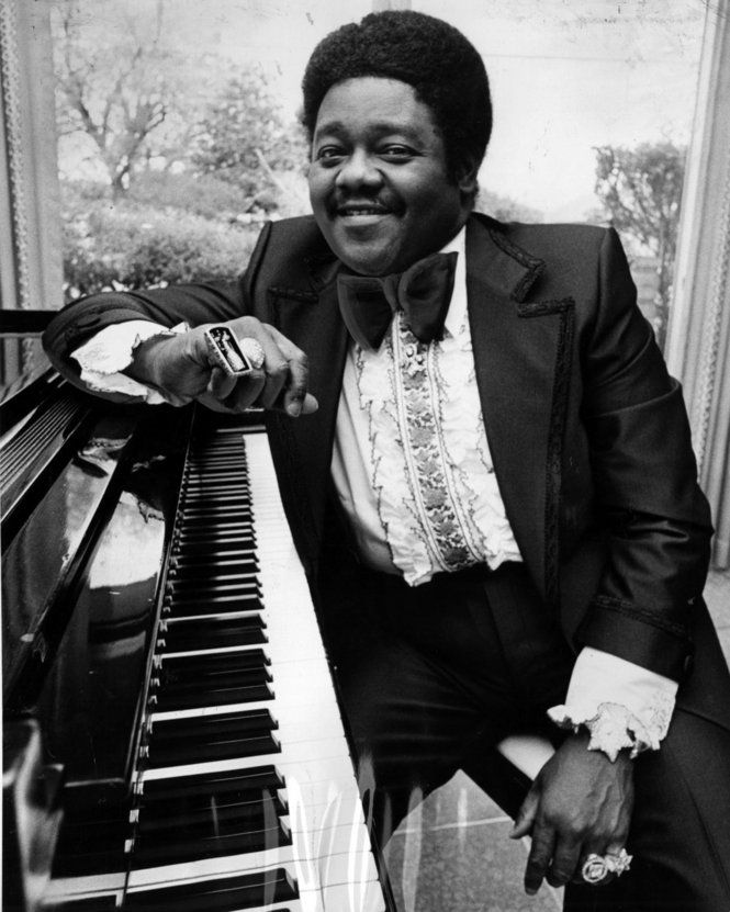 "Fats Domino, 1976: Antoine Dominique ""Fats"" Domino Jr. (February 26, 1928) is an rhythm and blues and rock and roll pianist and singer-songwriter. Domino released five gold (million-copy-selling) records before 1955. Domino also had 35 Top 40 American hits and has a music style based on traditional rhythm and blues ensembles of bass, piano, electric guitar, drums, and saxophone."