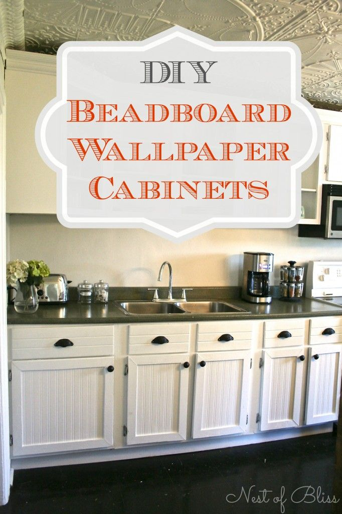 Use black handles to tie into black cooker  Transform old cabinets with this DIY beadboard wallpaper cabinet tutorial!