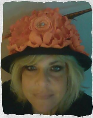 This is a bowler style hat with felt orange flowers.